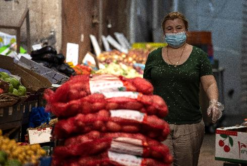 עסקים לא כרגיל. עובדת בחנות ירקות בשוק הישן באשקלון מנסה לתמרן בין ההנחיות המבלבלות של הסגר
