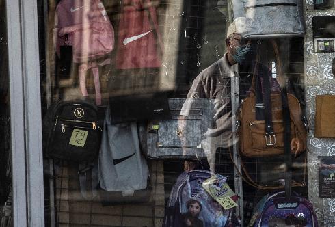 כמה רחוק מותר ללכת? אדם בודק את הגבולות מול חנות סגורה ברחוב באשקלון במהלך הסגר