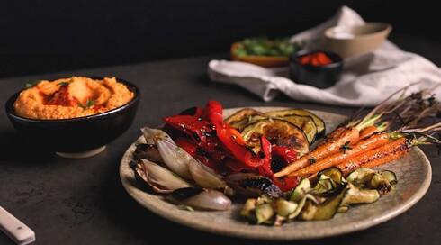 ירקות צלויים על מצע חומוס ועגבניות