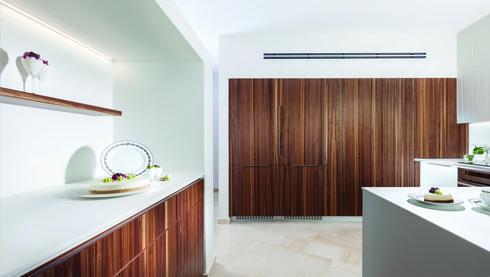 . במטבח נקי שפתוח לסלון עוצבו חזיתות מעץ אגוז אמריקאי, למראה המשכי מסוגנן. צילום: אלעד גונן